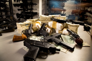 Pile of Guns drugs and Money