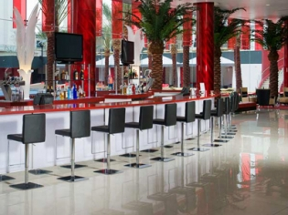 Palm trees among a red bar w/ black stools